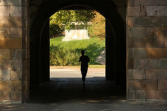 Silhouette of a runner in the shadow of gates Stock Photos