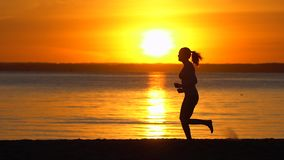 Silhouette of runner sporty woman running on sea ocean beach at sunset. Female jogger jogging in nature. Athletic girl stock video