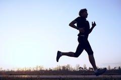 Silhouette runner on the sunrise sky Stock Images