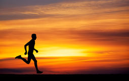 Silhouette of running man against the colorful sky. Royalty Free Stock Photos