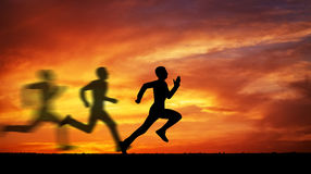 Silhouette of running man against the colorful sky. Stock Photography