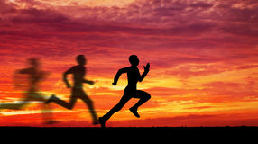 Silhouette of running man against the colorful sky. Royalty Free Stock Images