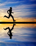 Silhouette of running man against the colorful sky. Silhouette of man running at sunset. Water reflection. Element of design Royalty Free Stock Photography