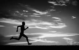 Silhouette of running man on cloudy sky. Black and white. Element of design Royalty Free Stock Photo