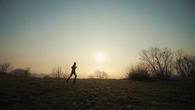 Silhouette of running man at the morning against the sunrise sunset. Morning sun on the background stock footage