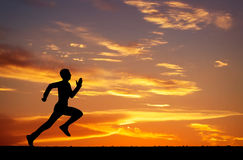 Silhouette of running man on sunset fiery background. Silhouette of running man against the colorful sky. Silhouette of running man on sunset fiery background Royalty Free Stock Photo