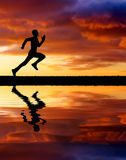 Silhouette of running man on sunset fiery background. Royalty Free Stock Image