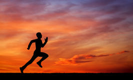 Silhouette of running man on sunset fiery sky background Stock Photography