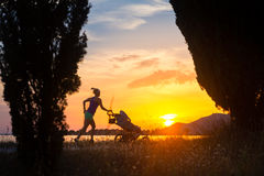 Silhouette of running mother with stroller enjoying motherhood a Royalty Free Stock Photos