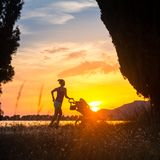 Silhouette of running mother with stroller enjoying motherhood a. Running mother with child in stroller enjoying motherhood at sunset and mountains landscape Royalty Free Stock Images