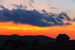 Silhouette of rural house on sunset sky. Background Stock Image