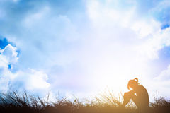 Silhouette of sad a woman depressed sitting alone on meadow. Stock Photography