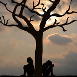 Silhouette of sad women sitting under the tree Stock Images