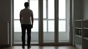 Silhouette of sad young adult stands near a big window at home stock footage