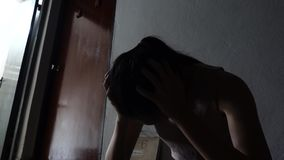 Silhouette of a sad young girl sitting in the dark leaning against the wall in old condo, Domestic violence, family problems stock video footage