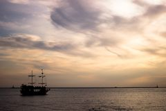Silhouette of a sailboat right at sunset on a calm support in the chain of the island. Ship and port at night stock images
