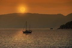 Silhouette of sailboat with sunset or sunrise. Background Royalty Free Stock Images