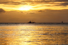 Silhouette of sailing boat on horizon of tropical sunset sea Philippines. Boracay island Stock Photography