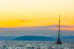 Silhouette of sailing boat at sunset Stock Photos