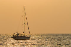 Silhouette of sailing yacht boat floating over sun set sky sea , Royalty Free Stock Photography