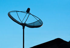 The silhouette of satelite dish for television in b;ue sky backg Royalty Free Stock Photography