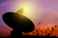 Silhouette of satellite dish on grass field Royalty Free Stock Images