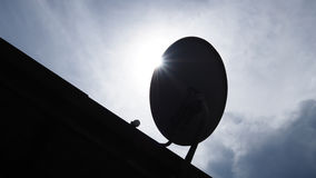 Silhouette satellite dish with sunlight on roof Stock Photography