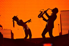 Silhouette of a saxophone player and and a woman singer on the s Stock Image