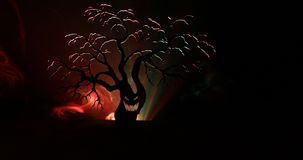 Silhouette of scary Halloween tree with horror face on dark foggy toned background with moon on back side. Scary horror tree with. Zombie and monster demon stock footage