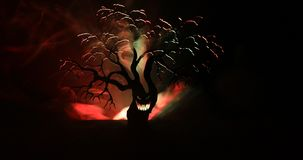 Silhouette of scary Halloween tree with horror face on dark foggy toned background with moon on back side. Scary horror tree with. Zombie and monster demon stock video footage