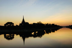 Silhouette scene of moat and Fort of Mandalay palace at sunset Stock Photo
