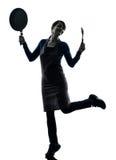 Silhouette se tenante à cuire heureuse de poêle de femme Photos libres de droits