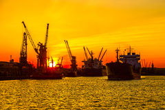 Silhouette of sea port cranes over sunset Stock Photos