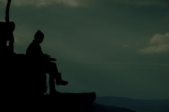 Silhouette Of A Seated Person. A silhouette of a seated person Stock Photo