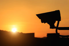 Silhouette of Security CCTV camera with sunset background Stock Image