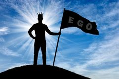 Concept of selfishness and narcissism. Silhouette of a selfish man with a crown on his head holds a flag with the word ego on top of a hill. The concept of Royalty Free Stock Image