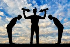Silhouette of a selfish man with a crown on his head is trying to attract attention. The servants worship him. The concept of a selfish and narcissistic Stock Photography
