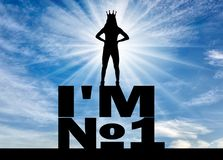 Concept of selfishness and narcissistic personality. Silhouette of a selfish and narcissistic woman with a crown on her head standing on a word I`m number one Royalty Free Stock Image
