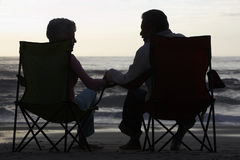 Silhouette Of Senior Couple Sitting On Beach In Deckchairs Royalty Free Stock Photography