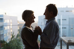 Silhouette of senior couple standing on balcony, holding hands Stock Image