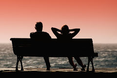 Silhouette seniors couple waiting for colourfull sunset Stock Images