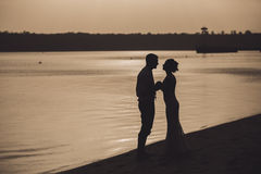Silhouette of sensual embracing young happy couple celebrating their love on the beach. Toned image stock photo