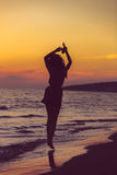 Silhouette of a sensual woman at sunrise on the beach, body, perfect figure, enjoying life Stock Photography