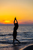 Silhouette of a sensual woman at sunrise on the beach, body, perfect figure, enjoying life Stock Photo