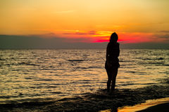 Silhouette of a sensual woman at sunrise on the beach, body, perfect figure, enjoying life Stock Images
