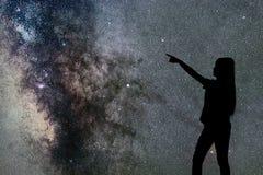 Silhouette seul de support de femme de la manière laiteuse et des étoiles de nuit photo stock