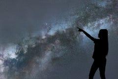 Silhouette seul de support de femme de la manière laiteuse et des étoiles de nuit images stock