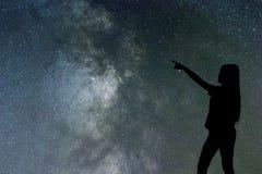 Silhouette seul de support de femme de la manière laiteuse et des étoiles de nuit photographie stock