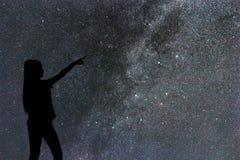 Silhouette seul de support de femme de la manière laiteuse et des étoiles de nuit image stock