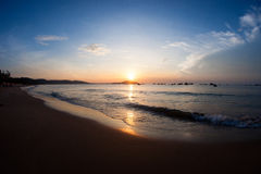 Silhouette of several small fishing boats at sea seen from sandy beach. Stock Photography